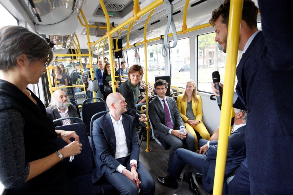 Genodigden bespreken de kansen voor een duurzamer openbaar vervoer, tijdens de eerst rit van de nieuwe elektrische bus op stadslijn 1 op 5 september 2017.